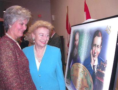 Lieutenant Governor Myra Freeman (left) and Princess Elettra Marconi-Giovanelli, Marconi's daughter, in Glace Bay, December 2002, admire a poster of a Canadian stamp commemorating the centennial of the first transatlantic wireless messages